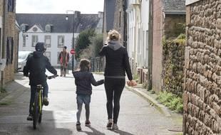 Une femme et ses deux enfants marchent dans une rue de Crac'h (Morbihan), commune touchée par le coronavirus où les écoles sont fermées.