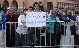 Un jeune homme tient une pancarte «Non au terrorisme» aux abords du café Argana, sur la place Jemaa el Fna de Marrakech, le 28 avril 2011.