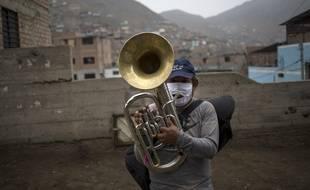 Un musicien joue du tuba en portant un masque avec un zip, à Lima, au Pérou, le 17 juillet
