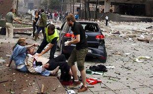 Un homme blessé est secouru après l'explosion qui a ravagé le centre d'Oslo, le 22 juillet 2011.