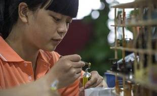 Une employée fabriquant un immeuble miniature dans l'usine Canyon Models à Shenzhen le 23 avril 2015