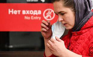 Une femme enlève son masque à la sortie du métro moscovite, le 13 octobre 2020.