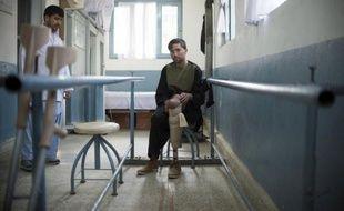"""Les mains serrées sur des barres parallèles, Mounir Ahmad, un sergent afghan de 23 ans mutilé par une mine, apprend à marcher avec une prothèse dans un centre orthopédique, au nord de Kaboul. """"L'armée ne faisait rien, dit-il. C'est ma famille qui m'a amené ici""""."""