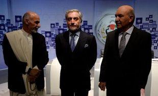 Les candidats à la présidentielle afghane Ashraf Ghani (gauche) et Abdullah Abdullah (centre) arrivent à un débat télévisé, le 8 février 2014 à Kaboul