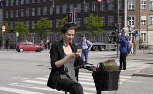 Une jeune femme regarde son téléphone alors qu'elle est sur son vélo (illustration).