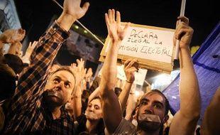 Des Espagnols portent du scotch sur la bouche lors d'une manifestation contre la crise économique et le chômage à la Puerta del  Sol, à Madrid, le 20 mai 2011.