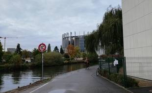 Au bord de l'eau, la piste cyclable qui va bientôt comporter de nouvelles grilles se trouve derrière un des bâtiments du Parlement, lui-même situé derrière le conseil de l'Europe.