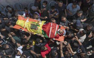 Des Palestiniens en deuil portent le corps d'Ahmed Jamil Fahed, tué par les forces israéliennes dans le camp de réfugiés d'al-Amari en Cisjordanie, à Ramallah, mardi 25 mai 2021.