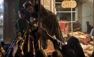 Des femmes et des enfants attendent des dons de pain devant une boulangerie à Kaboul le 24 septembre 2021