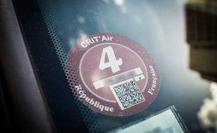 Une vignette Crit'Air 4, collée derrière le pare-brise d'une voiture diesel en stationnement