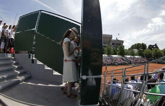 Une hôtesse à Roland-Garros s'occupe avec son téléphone portable.