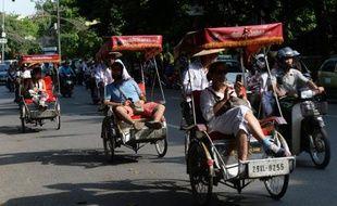 Des touristes se promènent en vélo dans Hanoï, le 16 juillet 2014