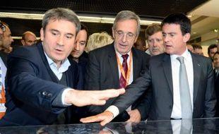 Le Premier ministre Manuel Valls (d) discute du projet de Grand Stade de rugby avec le maire de Ris-Orangis, Stéphane Raffalli (g) et celui d'Evry, Francis Chouat (c), le 4 décembre 2014 à Paris