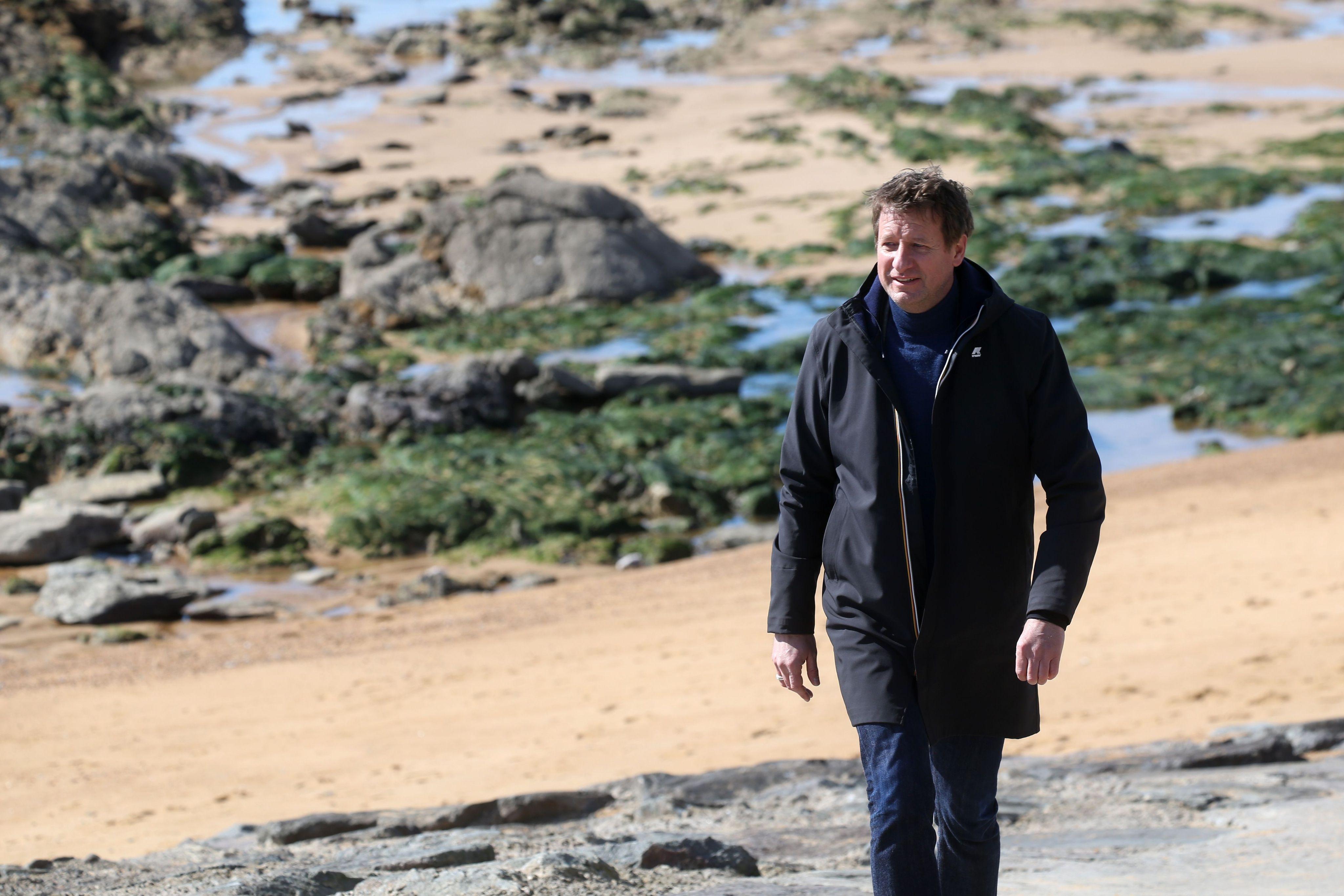 Yannick Jadot, seul sur le sable, les yeux dans l'eau.