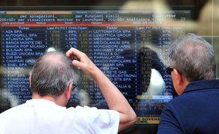 Deux personnes lisent les résultats de la Bourse de Milan le 11 juillet 2011.