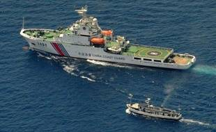 Un bateau garde-côte chinois (en haut) et un bateau de ravitaillement philippin se suivent à la trace le 29 mars 2014 près du récif de Second Thomas, en mer de Chine du sud, dont la souveraineté est réclamée par les deux pays