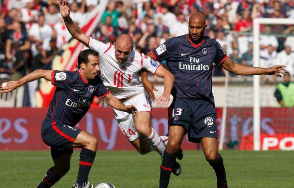 Les Parisiens Giuly (à g.) et Traoré (à dr.), autour du Lillois Vittek, lors d'un match de L1 le 30 août 2009 au Parc des Princes. – B.Tessier/REUTERS