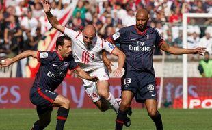 Les Parisiens Giuly (à g.) et Traoré (à dr.), autour du Lillois Vittek, lors d'un match de L1 le 30 août 2009 au Parc des Princes.