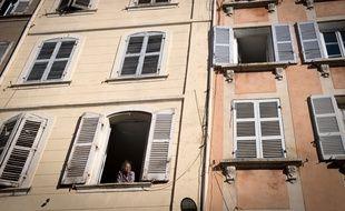 Une femme à la fenêtre d'un immeuble situé rue d'Aubagne à Marseille.
