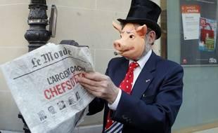 Un manifestant déguisé consulte le journal