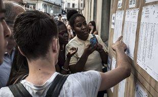 Des élèves scrutant les résultats du bac devant le lycée Ampère de Lyon, le 7 juillet 2015. AFP PHOTO / JEAN-PHILIPPE KSIAZEK