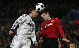 Les joueurs du Real Madrid, Cristiano Ronaldo (à g.) et de Manchester United, Robin Van Persie (à dr.) lors du match aller des huitièmes de finale de la Ligue des champions le 13 février 2013.