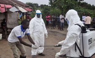 Des soignants se désinfectent après avoir été en contact avec des patients porteurs d'ebola au Liberia, le 30 juin 2015