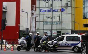 Des policiers devant le centre commercial Qwartz de Villeneuve-La-Garenne, dans les Hauts-de-Seine, le 13 juillet 2015
