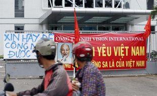Deux hommes à moto passent devant une usine de la province de Binh Duong, au Vietnam, où les vitres ont été brisées par les manifestations anti-chinoises, le 15 mai 2014.