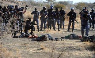 Des policiers sud-africains se tiennent près des corps de mineurs tombés après qu'ils aient ouvert le feu lors d'affrontements avec les manifestants à la mine de Marikana, le 16 août 2012 en Afrique du Sud