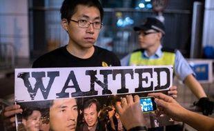 Un homme montre une affiche avec les photos des moliciers accusés d'avoir battu un manifestant, le 15 octobre 2014 à Hong Kong