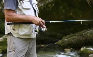 Un pêcheur au bord d'une rivière. Illustration.
