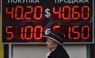 Une femme à Moscou passe devant un tableau indiquant les taux de change, le 13 octobre 2014