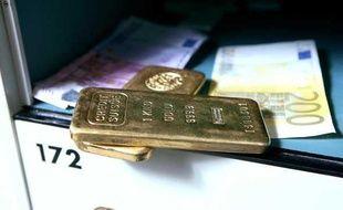 Lingots d'or et billets dans un coffre.