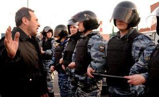 Un homme face aux policiers anti-émeutes dans le sud de Moscou, le 13 octobre 2013
