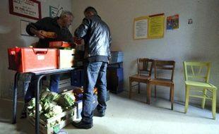 Un bénévole du Secours Catholique (g) distribue des colis de nourriture, le 4 décembre 2009 à Saint-Eloy-les-Mines