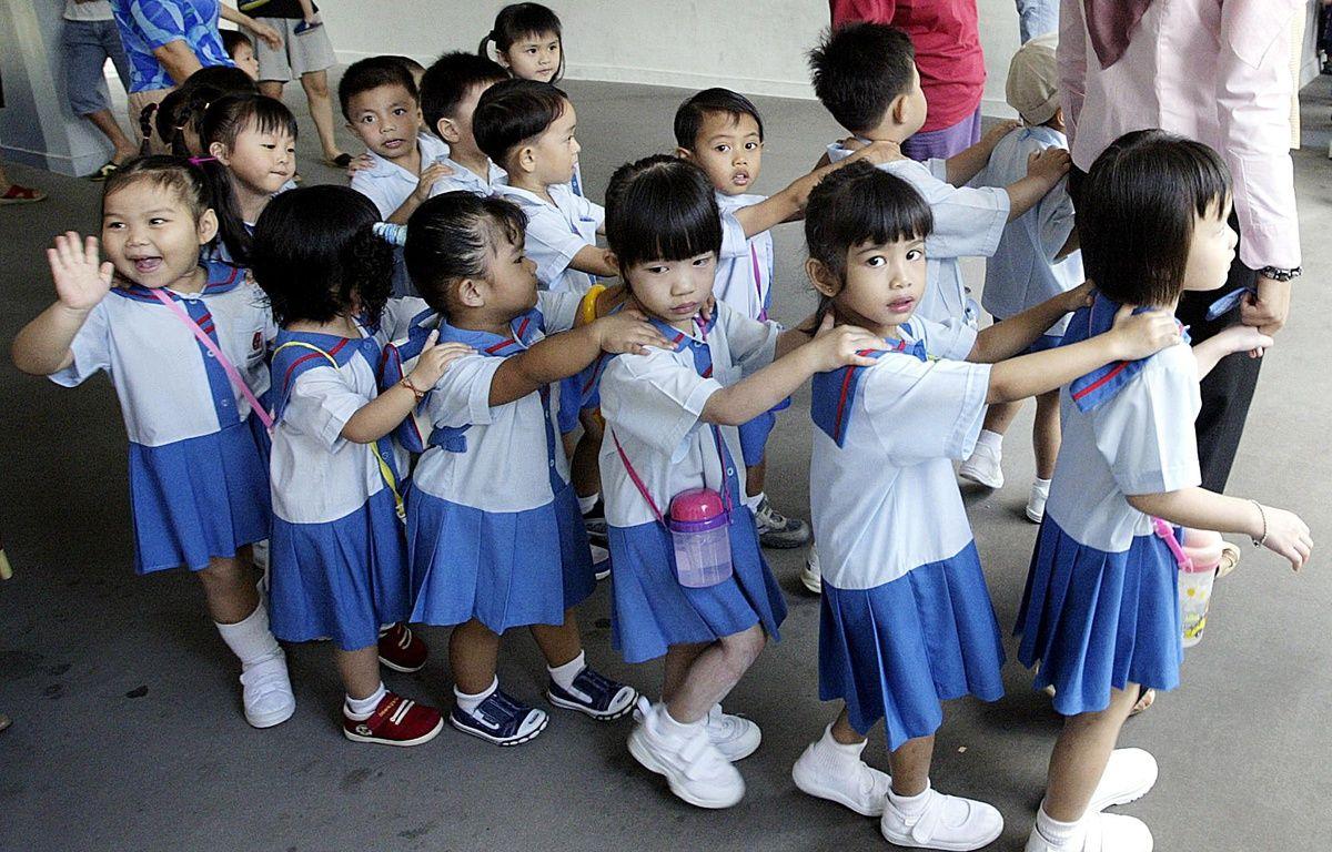 Les enfants de maternelle marchent jusqu'à leur salle de classe à Singapour. – ROSLAN RAHMAN / AFP
