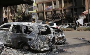 Une voiture calcinée devant le café Cappucino, visé, avec l'hôtel Splendid, par une attaque terroriste à Ouagadougou (Burkina faso), dans la nuit du 15 au 16 janvier 2016.