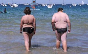 Deux personnes en surpoids se promènent sur la plage, en 2008