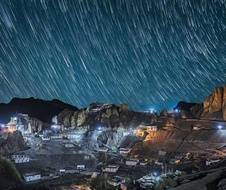 **MANDATORY BYLINE** Pic by Grey Chow/Caters News - (Pictured: The village of Dhankar in the Spiti Valley, Himachal Pradesh, northern India illuminated by streetlights as a sky of star trails fill the nights sky. Pic taken May 2018) - The Tibetan sky at night was captured in these beautiful images showing the locations stunning buildings and statues in the Himalayan Mountains. Grey Chow, 33, travelled for two hours to get to the Spiti Valley to capture the starry background drop along the deserted and isolated roads. The Senior Project Engineer was able to take amazingly clear images thanks to the limited amount of little pollution at an altitude of 4,500 foot.
