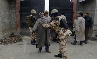 Des policiers pakistanais contrôlent un homme à Srinagar le 14 décembre 2014