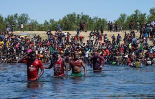 Des migrants haïtiens, faisant partie d'un groupe de plus de 10 000 personnes séjournant dans un campement du côté américain de la frontière, traversent le fleuve Rio Grande, à Del Rio, Texas, le 19 septembre 2021.