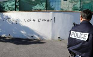 """Un policier devant un graffiti sur un mur""""Vice FN, non à l'Islam"""" à proximité de la mosquée de Béziers, le 8 octobre 2015"""