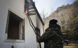 Un habitant met le feu à sa maison dans le village de Charektar.