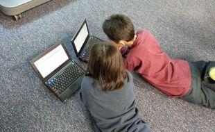 Deux enfants devant des écrans d'ordinateurs portables. Illustration