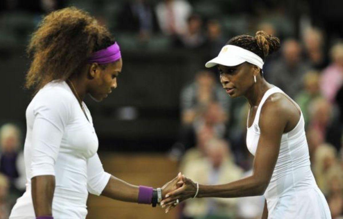 Serena Williams a gagné samedi l'épreuve du double dames de Wimbledon avec sa soeur Venus quelques heures après avoir remporté le simple. – Glyn Kirk afp.com