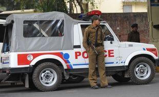 Un agent se tient devant une voiture de police, à New Delhi, le 4 février 2012.