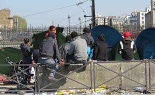 Des réfugiés aux abords de leurs tentes de fortune sous un pont de la ligne 2 du métro parisien à deux pas de la station Porte de la Chapelle.