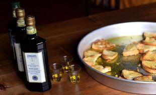 Des bouteilles d'huile d'olive et des morceaux de pain grillés en dégustation au pressoir de Cesare Buonamici, le 2 décembre 2014 à Fiesole, près de Florence, en Toscane