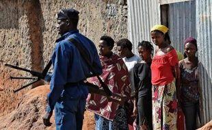 Des femmes regardent les policiers patrouiller dans les rues au lendemain d'une manifestion anti- Nkurunziza, le 2 juin 2015 à Bujumbura